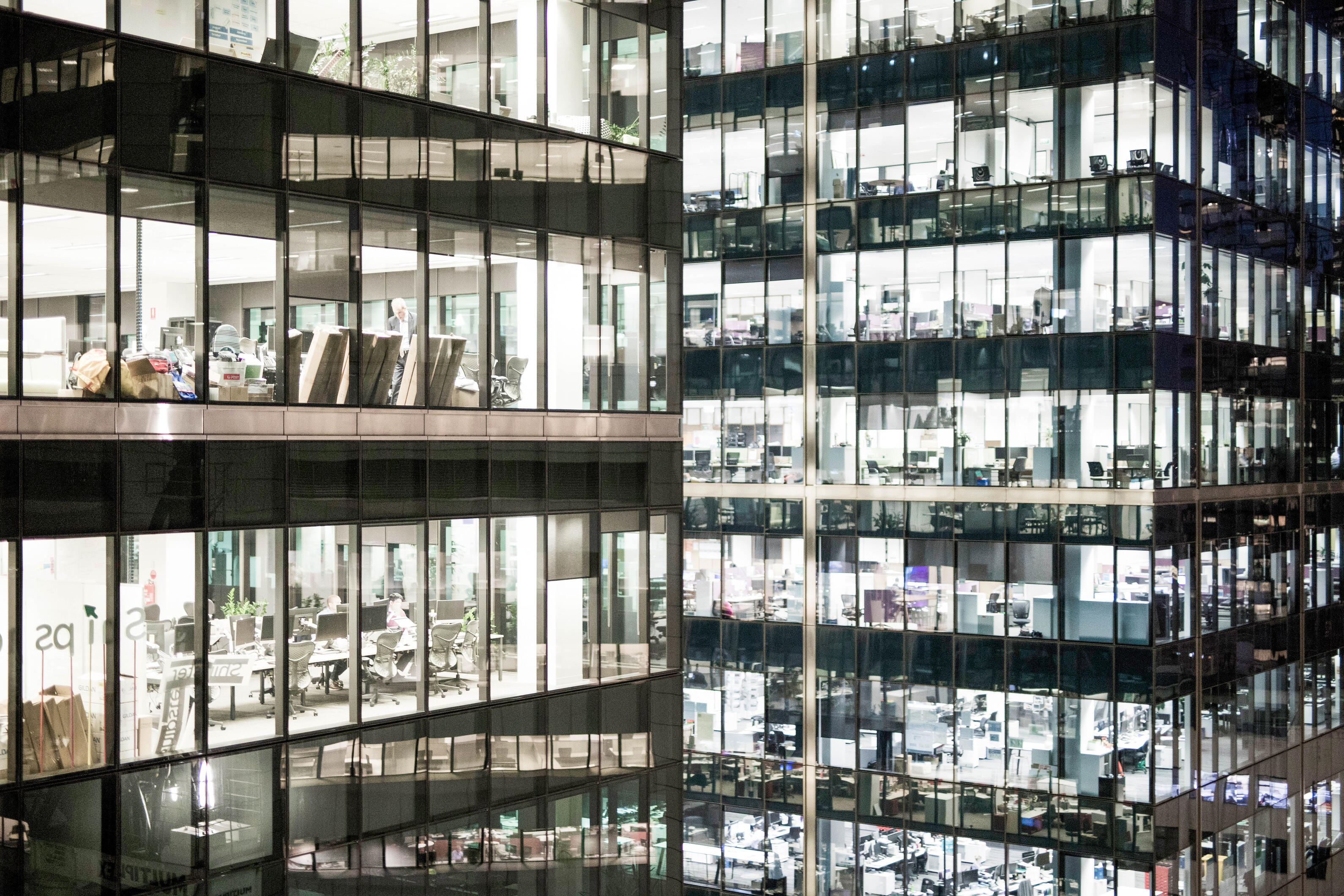 close-up-view-of-office-towers-at-nights-with-the-inside-fitout-business-desks-chairs-visible-bright_t20_xvQxj1